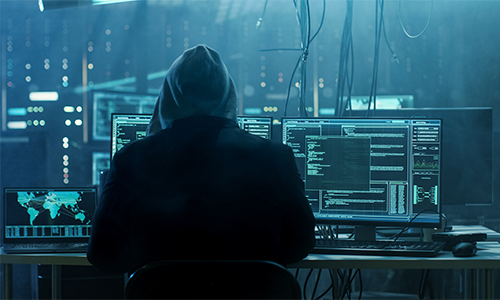 Hooded figure in a dark computer room